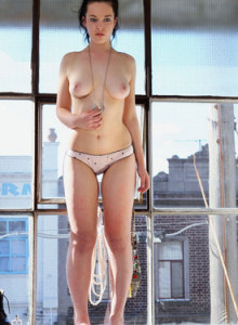 Exciting busty brunette Frances showing striptease by the window