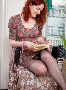 Redhead Jessie with the sexy legs covered with net pantyhose is reading a book and then showing her puffy nipples and hairy pussy