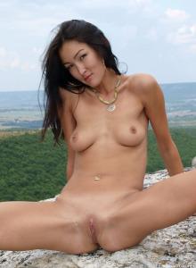 Asian girl in green bikini goes topless outside
